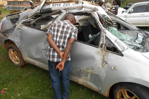 A man peeps through the wreckage of a car involved in the accident. PHOTO/COURTESY